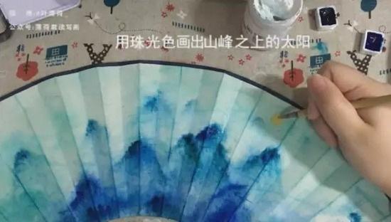 其实折扇画起来并不算太难,例如水彩山水画折扇画法,可以很随意,只要把握几个重点步骤,你也能画出好看的水彩画折扇,怎么画扇子?画扇面要注意什么?下面我们就一起来学习一下。 绘画折扇所用工具:  空白折扇;  刷水笔:新概念羊毛刷320;  颜料:mg蓝色系、绿色系分装,吉祥珠光,樱花白水粉;  毛笔:吴云辉欧颜柳赵大号毛笔、草帽崔勾线笔;  吹风机。 1.
