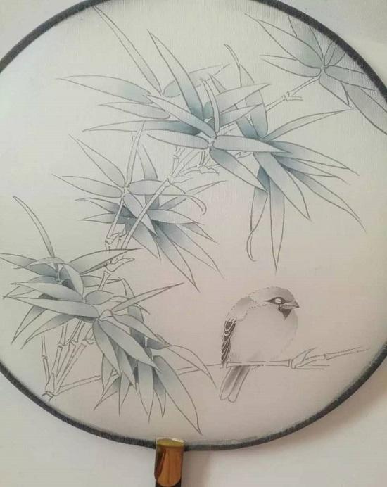 这幅画表现的是夏天的景色,手绘团扇画时要注意以下几点: 第一,竹叶的线条可以用铁线描,由于竹叶比较薄所以线条不能太粗了,另外竹叶一般很挺,翻转较少,因此工笔画竹子的线条要流畅挺拔、犀利。 第二,在工笔画染色时要注意恰到好处的表现夏天的竹叶郁郁葱葱,苍翠如滴的感觉。 第三,这幅团扇工笔画的竹子和麻雀形成了冷暖色的对比,使画面更加丰富和生动。但是竹子和鸟在颜色上还要有呼应,所以有些竹叶要提染赭墨色。 第四,画面要有虚实的变化。最上面的一组竹叶因为离我们比较远了,所以可以将颜色染淡一点,进行虚化处理。 竹子麻雀