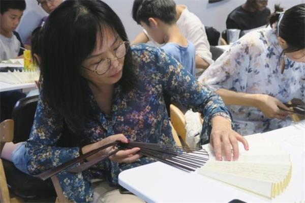 中国制扇工艺大师、苏州制扇技艺传承人盛春带领中外友人学制扇